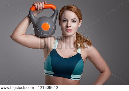 Young Fit Redhead Caucasian Woman Holding Kettlebell On Shoulder