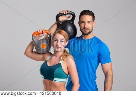 Young Caucasian Fit Couple Holding Kettlebells On Shoulder
