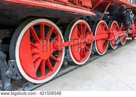 View of the old steam locomotive. Locomotive wheels in red color close-up.