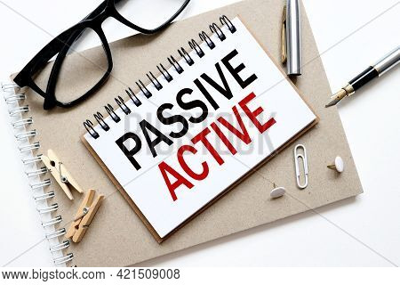 Active Instead Passive. Text On Paper, On A Notebook On A Craft Background, Near Glasses