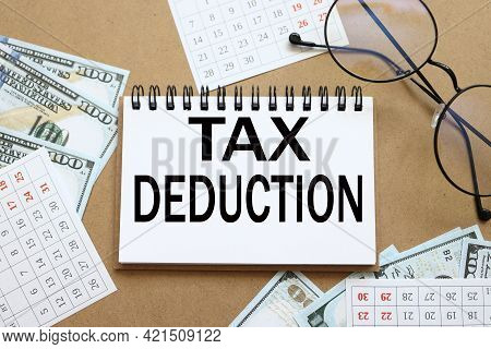 Tax Deduction. Text On White Notepad Paper Near Calendar On Wood Craft Background