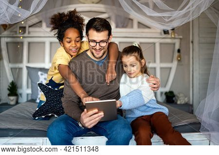Happy Family. Father And Multiethnic Children Playing On Tablet Pc At Home