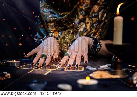 Cartomancy. A Fortune Teller Reads Tarot Cards. On The Table Are Candles And Fortune-telling Objects