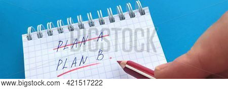 Banner With Future Plans Concept. I Have Plan B. Hand Holds A Red Pencil Over The Notepad With Cross