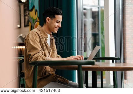 Young smiling hispanic man student sitting at the cafe table with laptop computer indoors