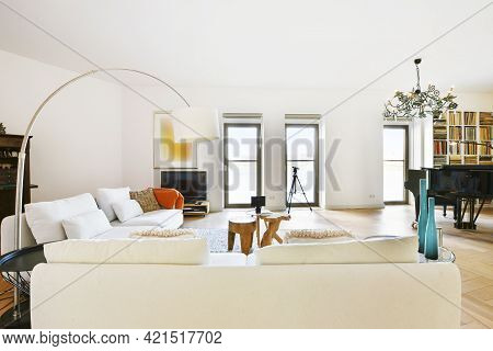 White Sofas And Tables On Carpet Against Piano Under Chandelier In Spacious Living Room Decorated Wi