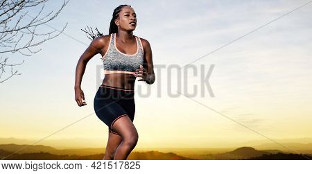 Close Up Action Portrait Of Young African Female Athlete Jogging. Muscular Girl In Sportswear Agains