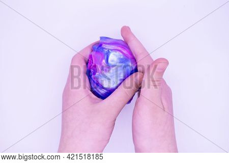Lose Up Of Game With Two-color Blue And Pink Slime In Someone Hands On A White Background. The Mucus