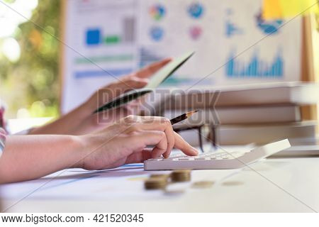 Young Entrepreneur Holding A Pencil And Calculate Saving, Finance, Passbook. Concept Of Time To Savi