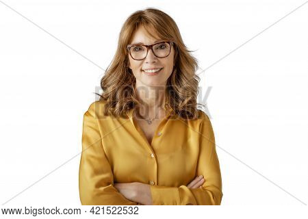Studio Portrait Of Middle Aged Attractive Woman Standing With Arms Crossed At Isolated White Backgro
