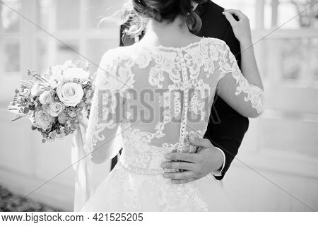 Black And White Photography. The Groom Hugs The Bride In A White Dress Around The Waist. Male Hand C