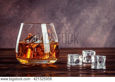 A Glass Of Whiskey Close Up. Brandy With Ice On A Brown Wooden Table. Cognac, Bourbon. Strong Alcoho