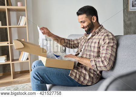 Happy Smiling Latin Indian Man Opening Box With Ordered Goods At Home On Couch. Online Shopper Male