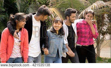 Group Of Five Happy Young Friends Laughing While Walking By Holding Hands - Concept Of Having Fun, B