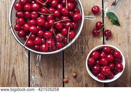Fresh Ripe Cherries In A Bowl On A Wooden Table.