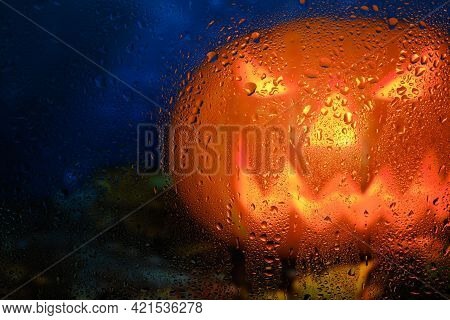 Halloween Pumpkin With Burning Eyes Behind The Autumn Window Wet With Raindrops