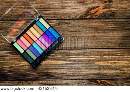 Multi-colored Palette Of Eye Shadows On A Wooden Background. Make-up For The Eyelids.