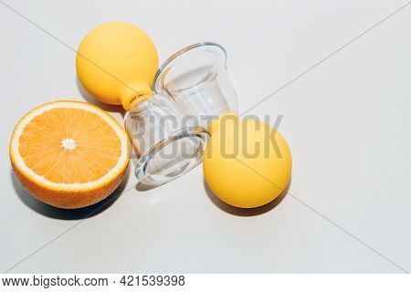 Vacuum Massage Anti-cellulite Cups On A Gray Background With An Orange. Self-massage For Healthy Ski