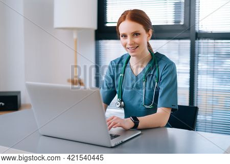 Portrait Of Cheerful Smiling Young Female Doctor In Blue Green Medical Uniform Typing On Laptop Comp