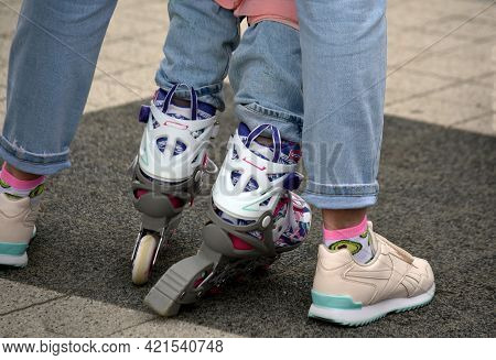 Mom In Light Jeans And Sneakers Teaches Daughter In Jeans And Roller Skates To Roller Skate Feet In
