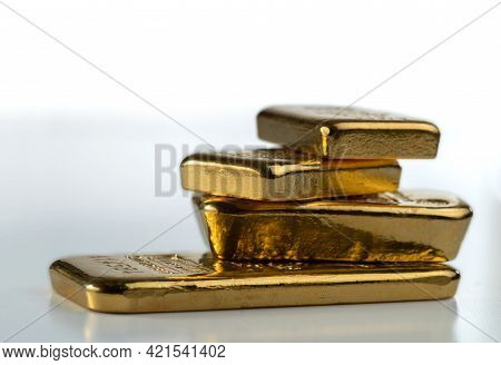 Four Gold Bars Of Various Weights On A Light Background. Selective Focus.