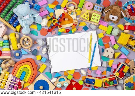 Educational Wooden Plastic And Fluffy Kids Toys And Blank Notebook With Colored Pencils On Gray Back