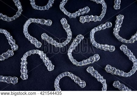 Transparent Invisalign Retainers Brackets Pattern On Black Background. Dental Invisible Orthodontic