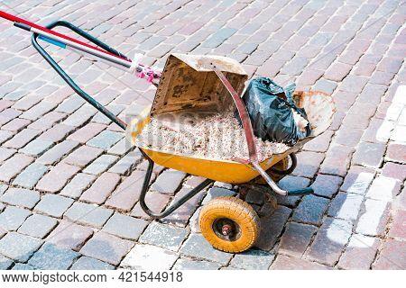 Blossom Petals Lays Inside A Wheelbarrow On The Cobblestone Street Ground. Huge Dustpan. Plastic Bag