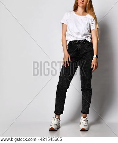 Studio Shot Of Unrecognizable Stylish Young Woman In Black Jeans And White T-shirt. Fashionable Woma