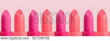 Lipsticks In A Row On A Pink Background Banner. Close-up Of Pink And Wine Lipsticks.