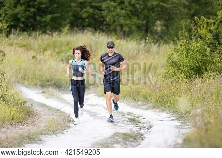 Sporty Man And Woman Run On The Country Road