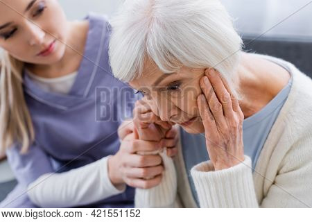 Young Nurse Touching Hand Of Elderly Woman, Suffering From Dementia And Sitting With Bowed Head, Blu
