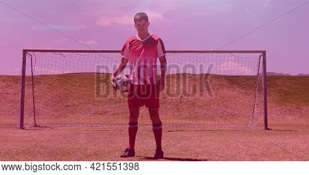 Composition of footballer holding ball on football pitch with pink background. sport, fitness and active lifestyle concept digitally generated image.