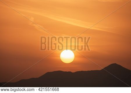 Sunset Sky With Orange Clouds. A Beautiful, Colorful, Abstract Mountain Landscape With Sun In A Oran
