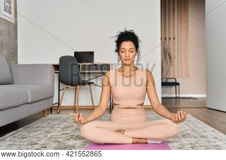 Young Healthy African American Mixed Race Girl Sitting On Mat At Home In Lotus Pose Meditating Breat