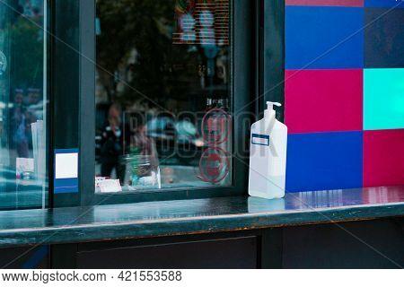Window Of Outdoor Coffee Shop To Sell Take-away Coffee With Hand Sanitiser On Windowsill. Customer.