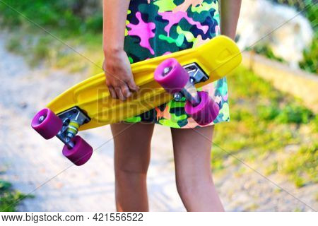 Defocus Girl Holding Yellow Penny Board. View From Back. Summer Bright Colors. Child Hands Holding S