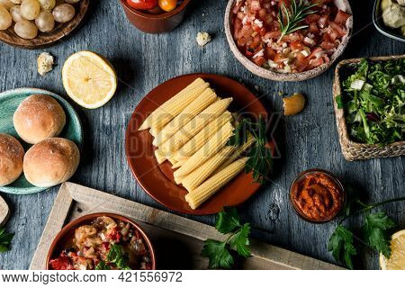 high angle view some different vegan snacks, dips such as guacamole or sweet potato sobrasada, side dishes, and some other ingredients to prepare vegan sandwiches, on a gray rustic wooden table