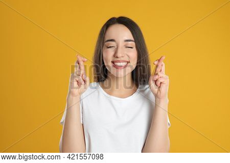 Excited Young Woman Holding Fingers Crossed On Yellow Background. Superstition For Good Luck
