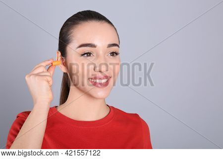 Young Woman Inserting Foam Ear Plug On Grey Background. Space For Text