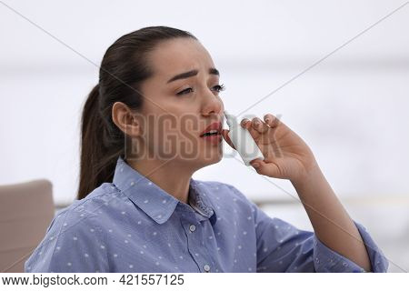 Sick Young Woman Using Nasal Spray In Office