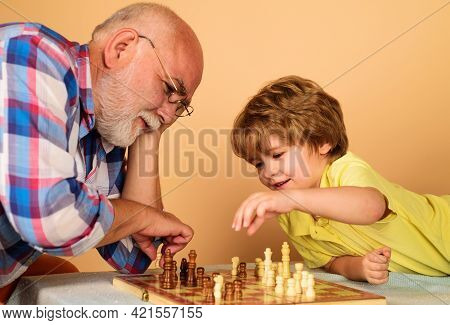 Child Boy Developing Chess Strategy. Grandfather And Grandson Playing Chess. Brain Development And L
