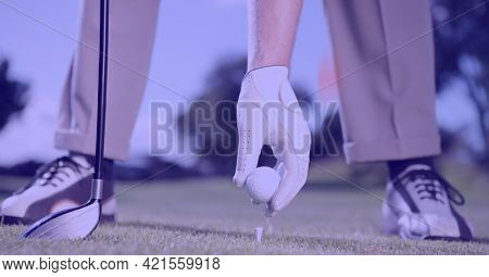 Composition of low section of male golf player with club holding golf ball in golf course. sport, fitness and active lifestyle concept digitally generated image.