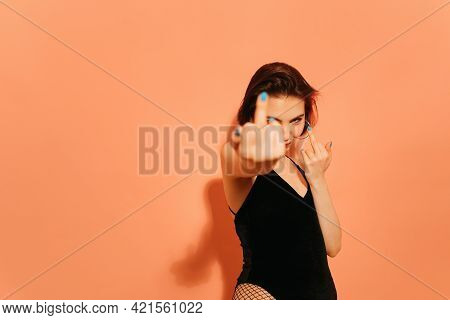 Young Woman With Provocative Middle Fingers Gesture On Orange Background.