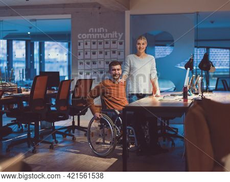 Businessman in a wheelchair in modern coworking office space working late night in office. Colleagues in background. Disability and handicap concept.