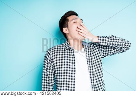 Asian Student In A Plaid Shirt Falls Asleep And Yawns Covering His Mouth With His Hand Out Of Boredo