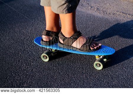 Defocus Skater Moving Along Asphalt Road On A Yellow Skateboard Wearing Black Sandals. Some Of The L