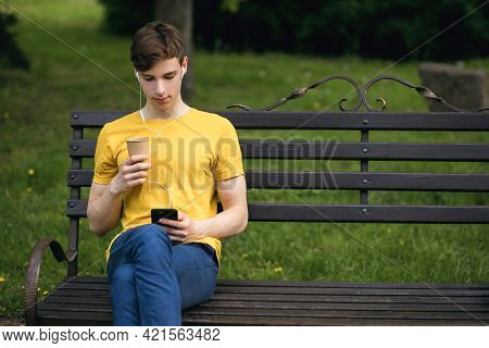 A Young Guy Is Resting In The Park Sitting On A Bench And Listening To Music On Headphones. A Young