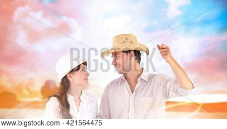 Composition of happy holiday couple wearing hats smiling at each other, over sunset sky. free time, holiday and leisure lifestyle concept digitally generated image.