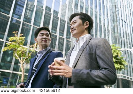 Side View Of Two Asian White Collar Office Worker Discussing Business While Walking In Street In Dow